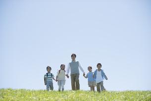 草原で手をつなぐ小学生と先生の写真素材 [FYI04549219]