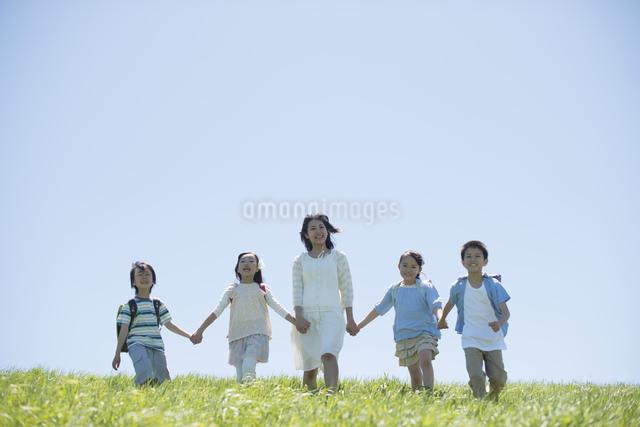 草原で手をつなぐ小学生と先生の写真素材 [FYI04549225]