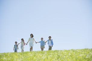 草原で手をつなぐ小学生と先生の写真素材 [FYI04549236]
