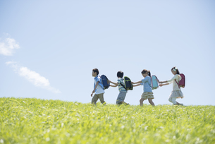 草原を歩く小学生の写真素材 [FYI04549246]