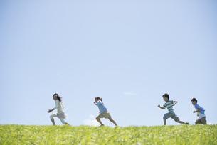 草原を走る小学生の写真素材 [FYI04549251]