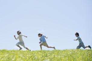 草原を走る小学生の写真素材 [FYI04549252]