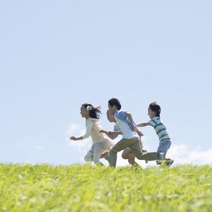 草原を走る小学生の写真素材 [FYI04549253]