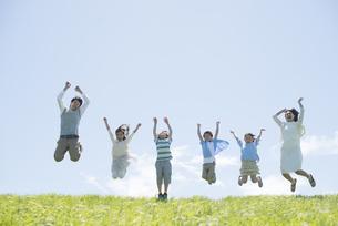 草原でジャンプをする小学生と先生の写真素材 [FYI04549259]