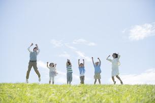 草原でジャンプをする小学生と先生の写真素材 [FYI04549262]