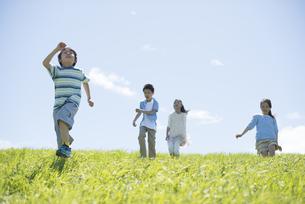 草原を走る小学生の写真素材 [FYI04549267]