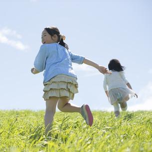 草原を走る小学生の後姿の写真素材 [FYI04549270]