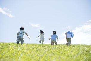 草原を走る小学生の後姿の写真素材 [FYI04549271]