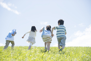 草原を走る小学生の後姿の写真素材 [FYI04549277]