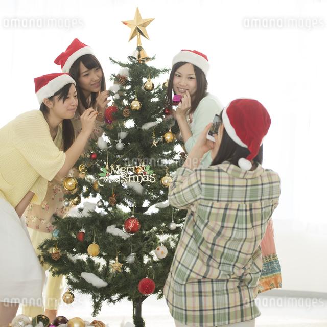 クリスマスツリーの周りで写真を撮る4人の女性の写真素材 [FYI04549290]