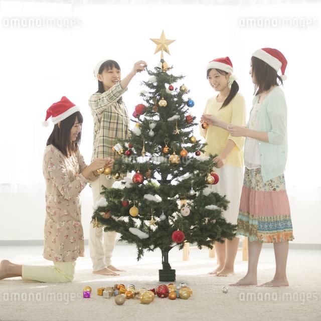 クリスマスツリーの飾り付けをする4人の女性の写真素材 [FYI04549297]