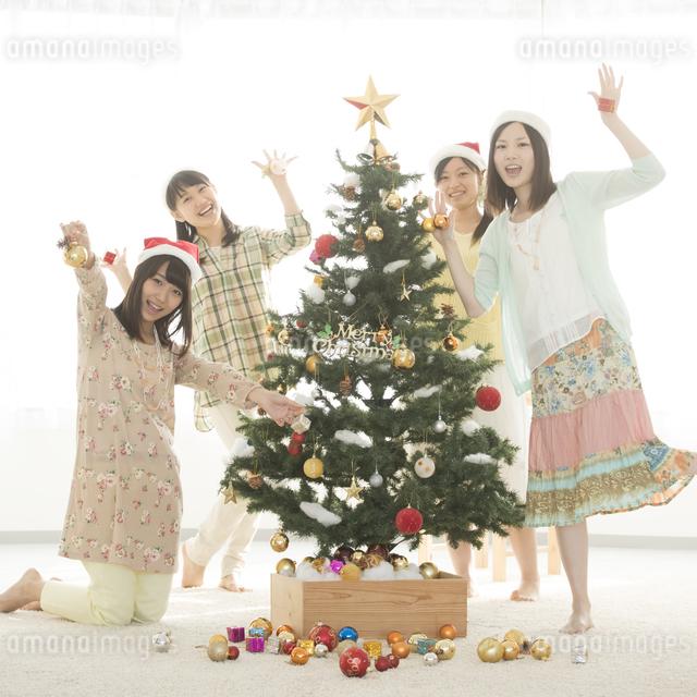 クリスマスツリーの飾り付けをする4人の女性の写真素材 [FYI04549298]