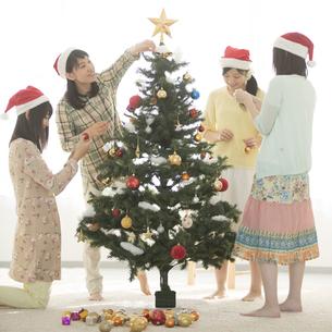クリスマスツリーの飾り付けをする4人の女性の写真素材 [FYI04549300]