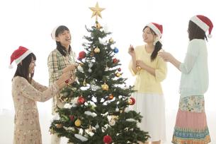 クリスマスツリーの飾り付けをする4人の女性の写真素材 [FYI04549301]