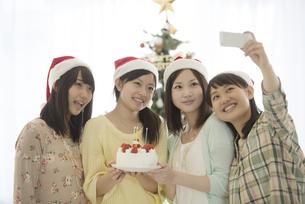 ケーキを持ち自撮りをする4人の女性の写真素材 [FYI04549319]