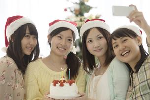ケーキを持ち自撮りをする4人の女性の写真素材 [FYI04549324]