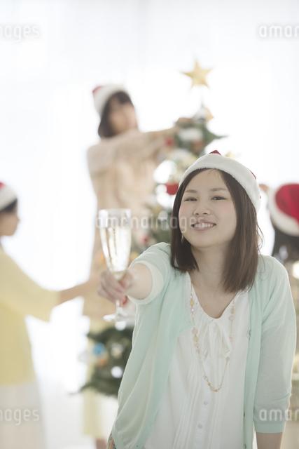 シャンパンを持ち微笑む女性の写真素材 [FYI04549328]