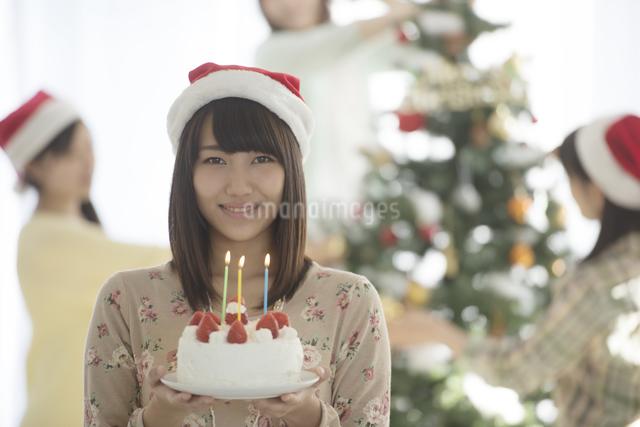 ケーキを持ち微笑む女性の写真素材 [FYI04549330]