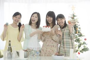 ケーキとクリスマスグッズを持ち微笑む4人の女性の写真素材 [FYI04549338]