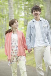 新緑の中で散歩をするカップルの写真素材 [FYI04549371]