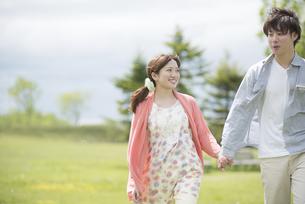 公園で散歩をするカップルの写真素材 [FYI04549375]