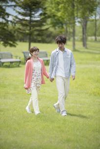 公園で散歩をするカップルの写真素材 [FYI04549379]