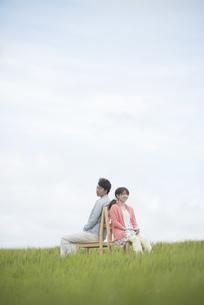 草原で椅子に座り音楽を聴くカップルの写真素材 [FYI04549386]