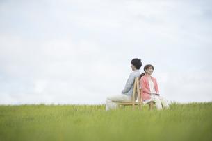 草原で椅子に座り音楽を聴くカップルの写真素材 [FYI04549388]