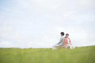 草原で椅子に座り音楽を聴くカップルの写真素材 [FYI04549390]