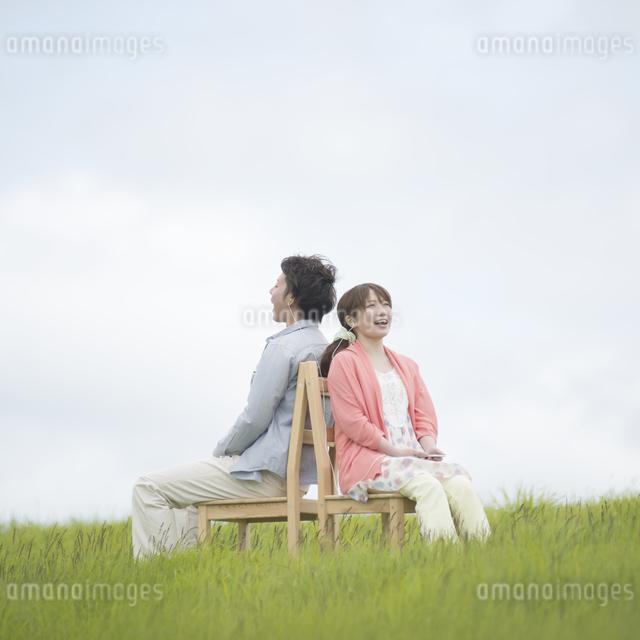 草原で椅子に座り音楽を聴くカップルの写真素材 [FYI04549391]