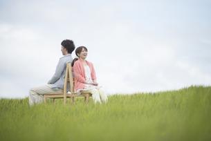 草原で椅子に座り音楽を聴くカップルの写真素材 [FYI04549392]
