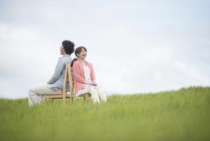 草原で椅子に座り音楽を聴くカップルの写真素材 [FYI04549394]