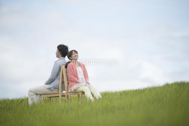 草原で椅子に座り音楽を聴くカップルの写真素材 [FYI04549395]