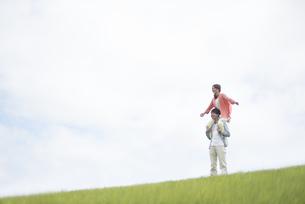 草原で肩車をするカップルの写真素材 [FYI04549412]