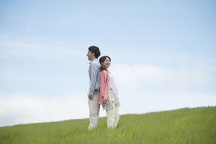 背中合わせに立つカップルの写真素材 [FYI04549427]
