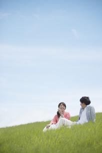 草原で談笑をするカップルの写真素材 [FYI04549438]