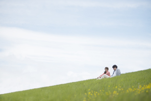 草原で談笑をするカップルの写真素材 [FYI04549445]