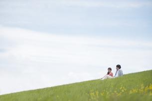 草原で談笑をするカップルの写真素材 [FYI04549448]