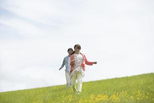 草原を走るカップルの写真素材 [FYI04549469]