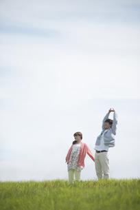 草原でリラックスをするカップルの写真素材 [FYI04549493]