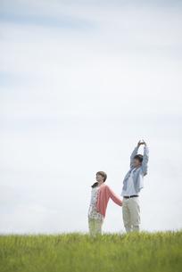 草原でリラックスをするカップルの写真素材 [FYI04549494]