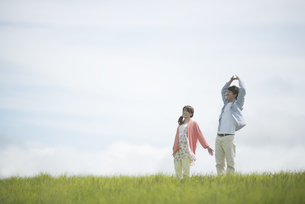 草原でリラックスをするカップルの写真素材 [FYI04549495]
