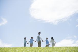 草原で手をつなぐ小学生と先生の写真素材 [FYI04549501]