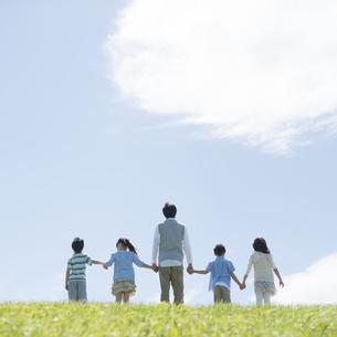 草原で手をつなぐ小学生と先生の後姿の写真素材 [FYI04549503]