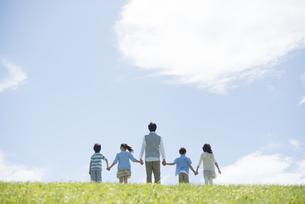 草原で手をつなぐ小学生と先生の後姿の写真素材 [FYI04549504]