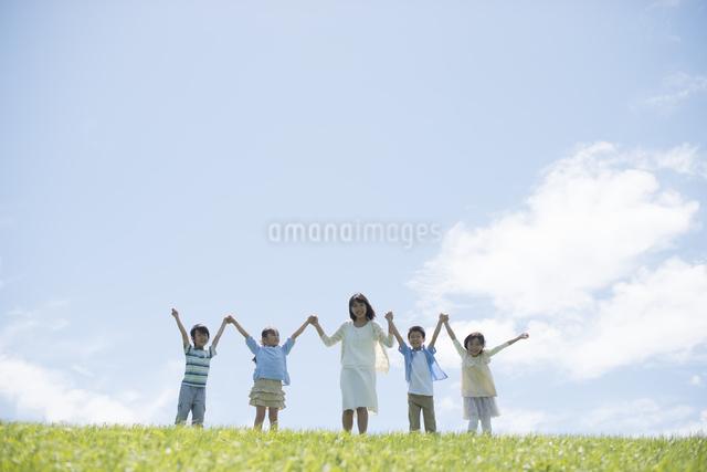 草原で手をつなぐ小学生と先生の写真素材 [FYI04549518]