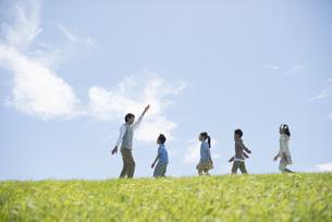 草原を歩く小学生と先生の写真素材 [FYI04549545]
