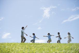 草原を歩く小学生と先生の写真素材 [FYI04549555]