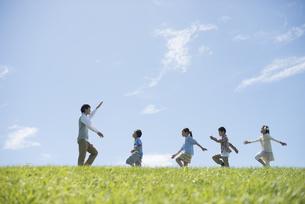 草原を歩く小学生と先生の写真素材 [FYI04549558]