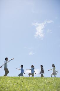 草原を歩く小学生と先生の写真素材 [FYI04549561]